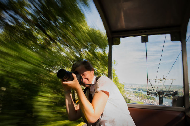 Side view of woman photographing in overhead cable car