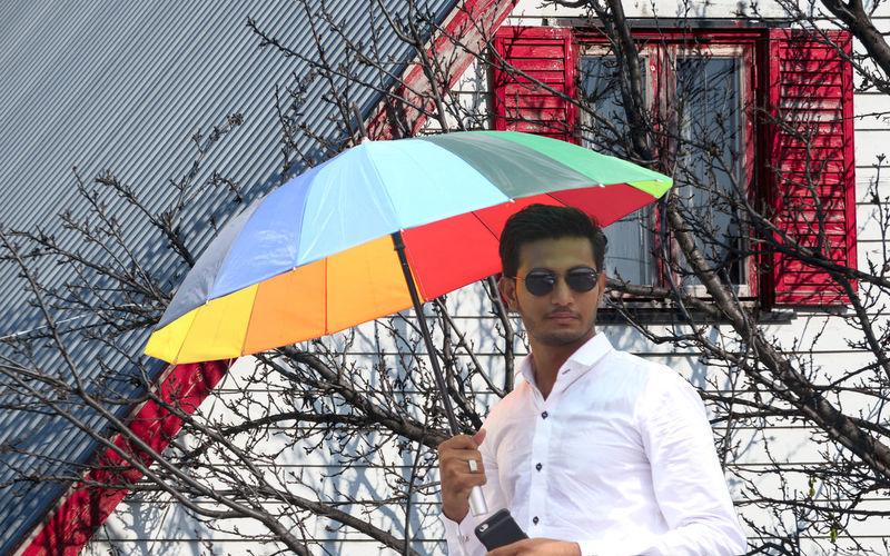 Portrait of young man holding umbrella