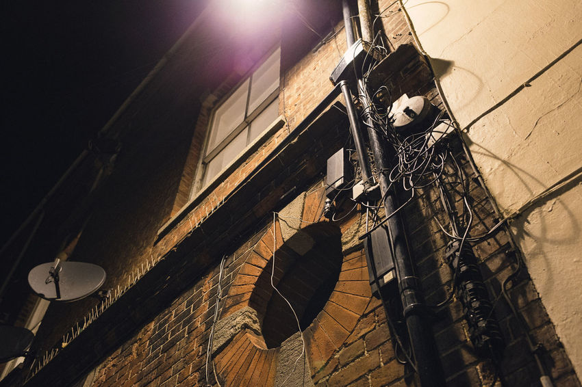 Late night image of messy wiring on a house exterior. Architecture Home House Illuminated Mess Messy Night Night Lights Night Photography Nightphotography Nighttime No People Outdoors Outside Outside Wall Satellite Dish Window Wires