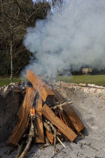 High angle view of bonfire on land against trees