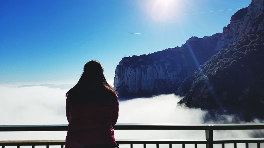 Rear view of woman standing against cloudscape at observation point