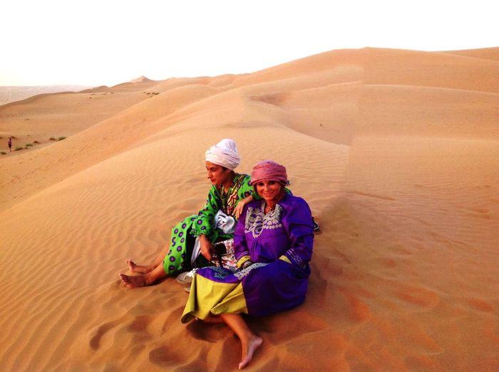 Women sitting on sand dune in desert