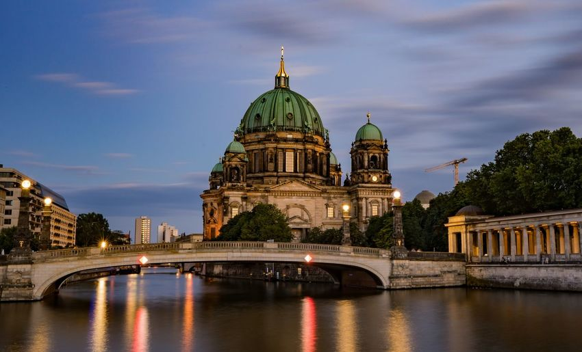 View of river by berlin cathedral against clear sky during sunset