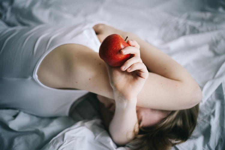 High angle view of woman with apple lying on bed at home