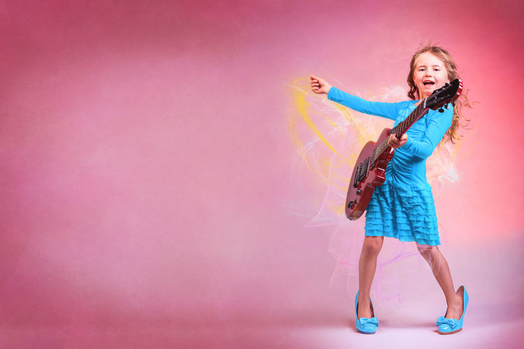 Girl Playing Guitar Over Colored Background