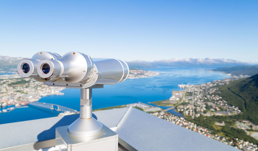Coin-operated binoculars against sea during sunny day