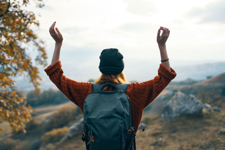 Rear view of woman with arms outstretched standing on mountain