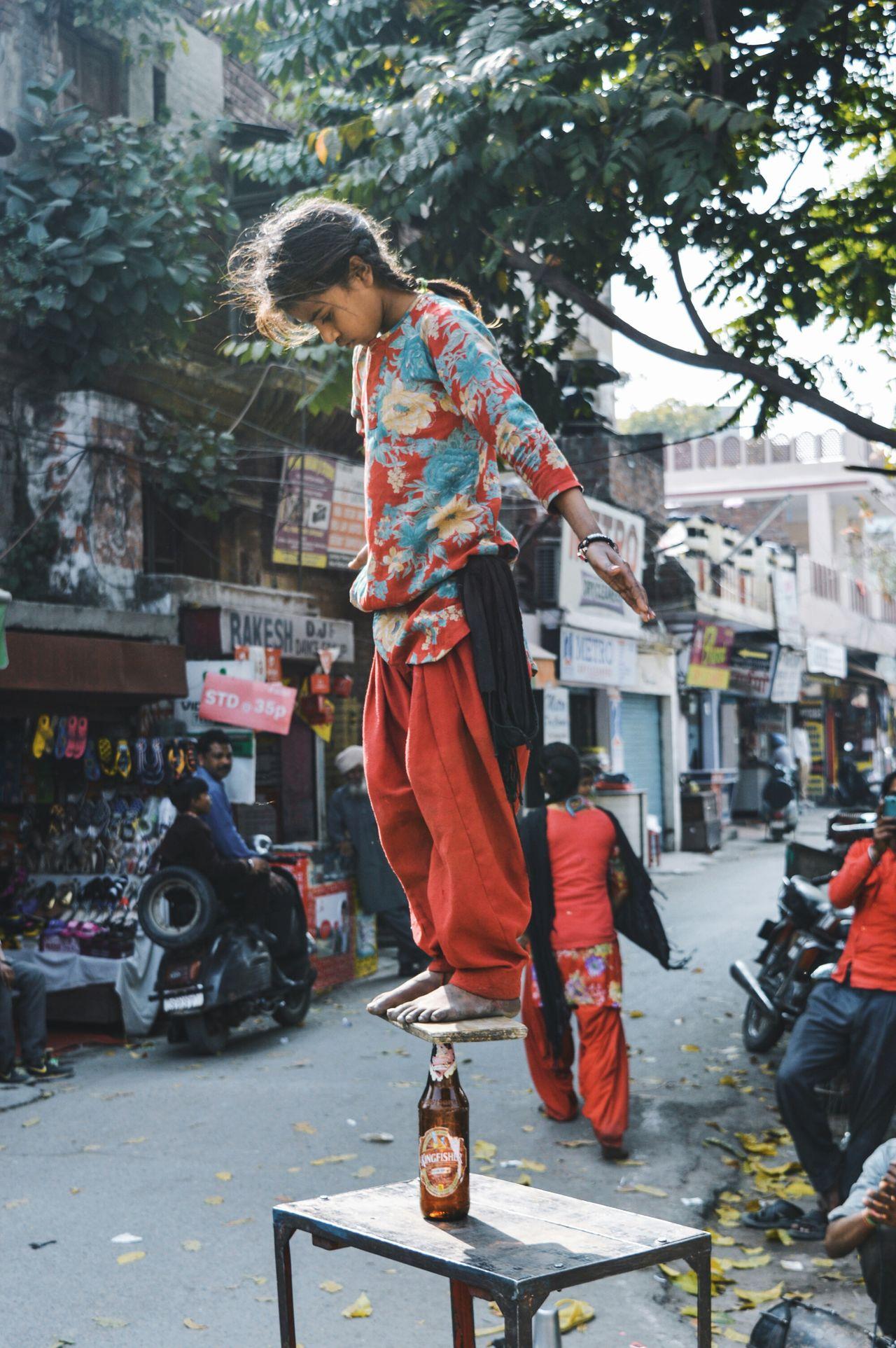 Full length of poor girl showing stunt on street