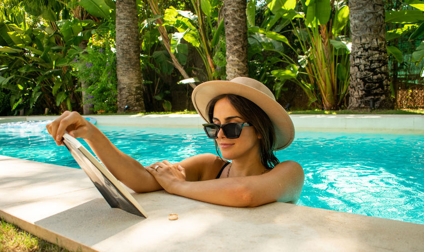 Young woman wearing sunglasses in swimming pool against trees