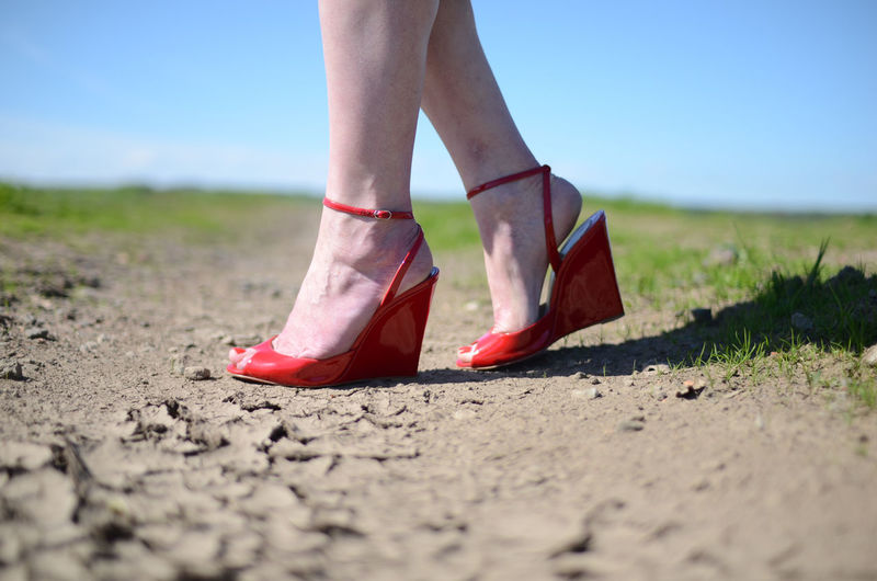 Low Section Human Leg One Person Human Body Part Body Part Shoe Day Women Land Nature Lifestyles Selective Focus Adult Grass Real People Sky Surface Level Leisure Activity Standing Outdoors Human Foot Human Limb High Heels Red Shoes