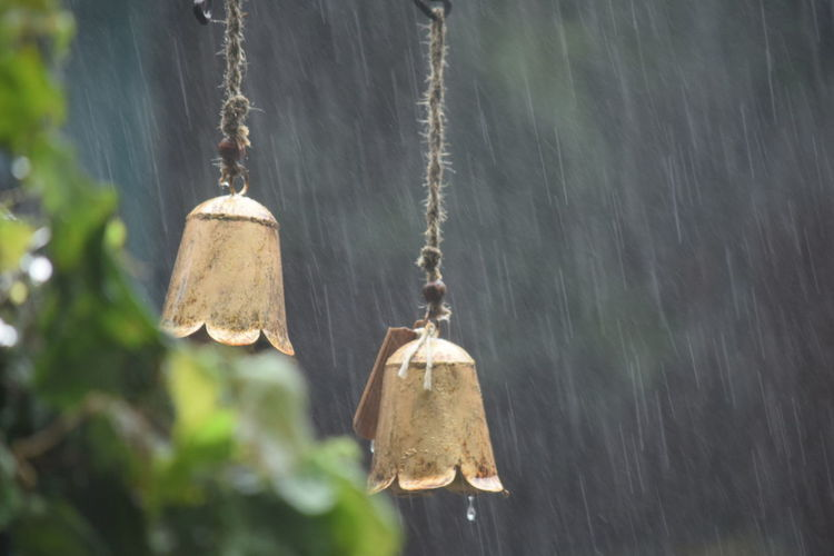 Metallic Bells Hanging Outdoors During Monsoon