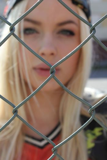Close-up portrait of young woman seen through chainlink fence