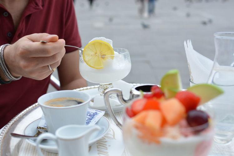 Midsection of man having drink at sidewalk cafe