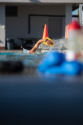 Swimmer in training showing just one arm with paddles Swimming Training Swimming Pool Outdoor Pool One Person Water Human Body Part Motion Pool Selective Focus Surface Level Swim Swimmer Paddle