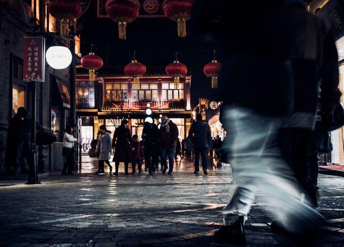 Crowd in illuminated city at night