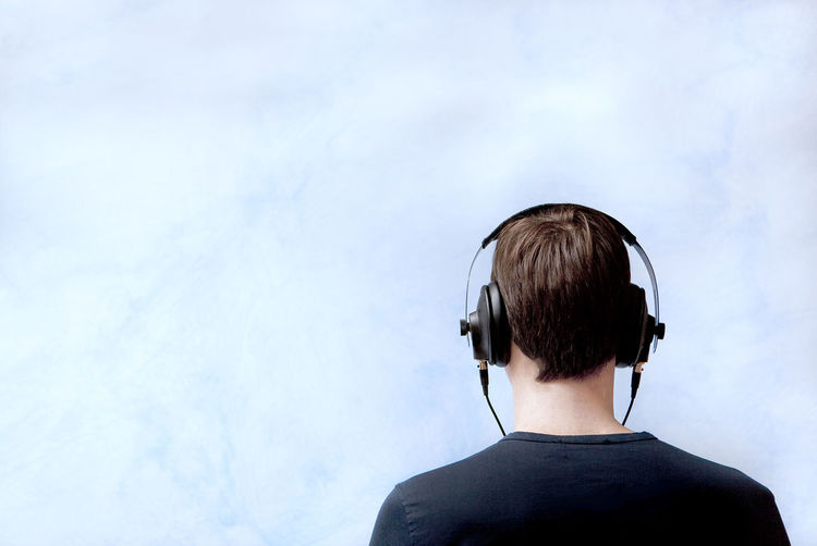 Rear view of young man listening music while standing against cloudy sky
