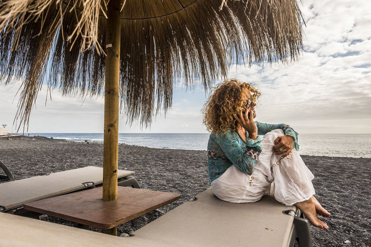 Woman talking on mobile phone at beach