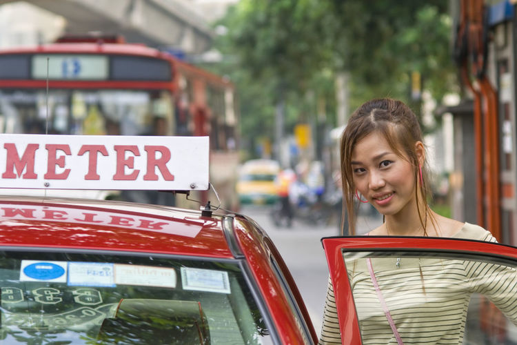 Portrait of beautiful woman by taxi in city