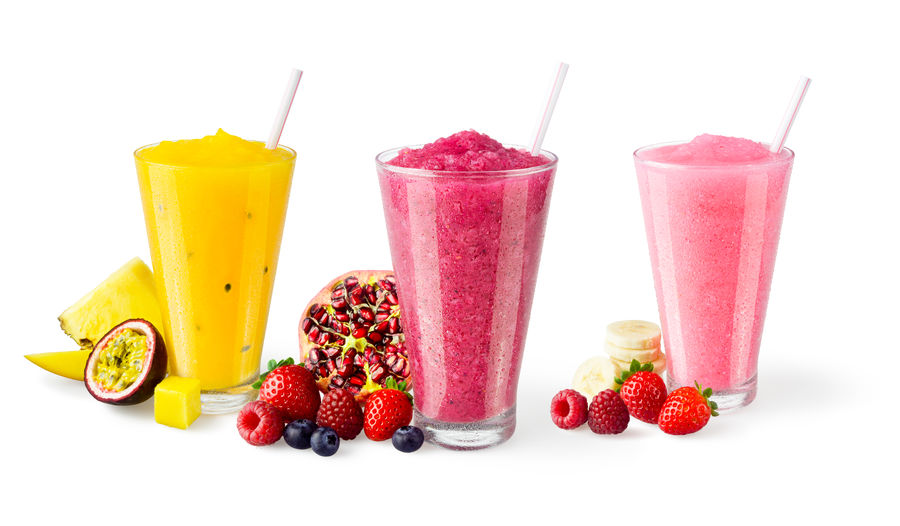 Close-up of various fruit drinks against white background