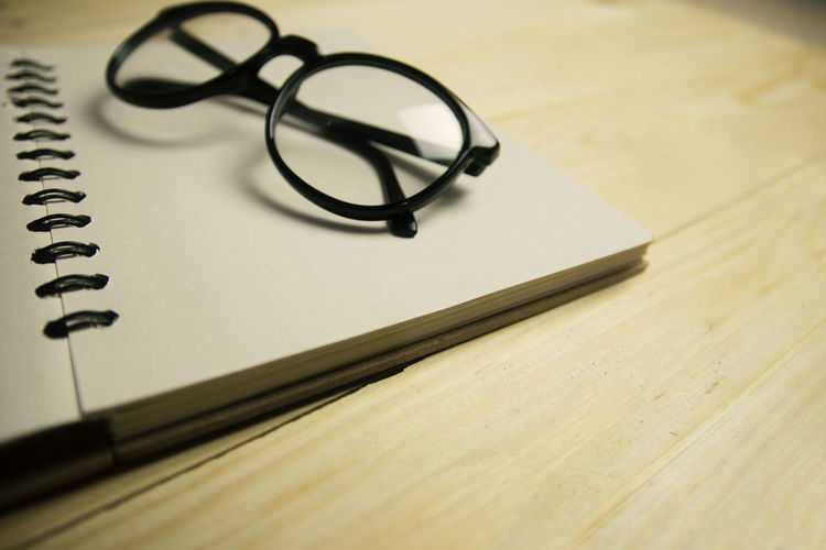 Close-up of eyeglasses on spiral notebook at table