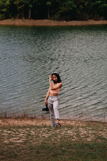 Portrait of smiling young woman standing in lake