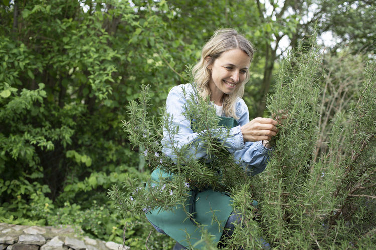 Smiling woman standing by plants against trees