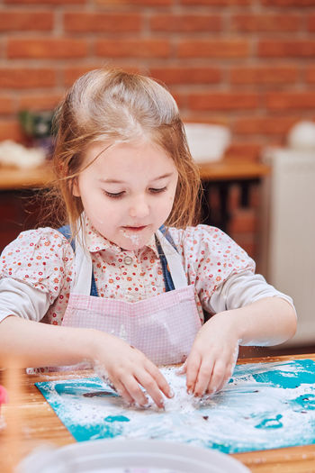 Close-up of girl looking at table