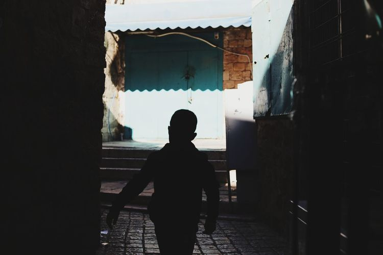 Rear view of silhouette boy walking on footpath against building