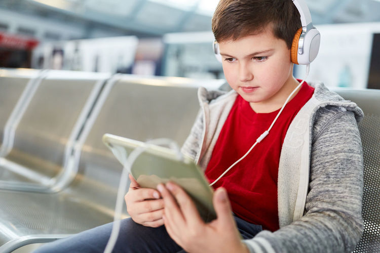 Boy with headphone and tablet listens to music in wait before the flight in the airport Child Tablet Airport Headphones Music Listen Streaming App Wait Trip Waiting Time Boy Flight Stopover Audiobook Music Streaming Technology Network Social Media Travel Mp3 Traveller Rest Area Holiday Vacation Railroad Station Station On The Way Sit Terminal Waiting Area Transportation People Tourism Fly Airline Caucasian