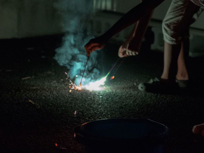 Low Section Of Man Burning Sparklers On Street