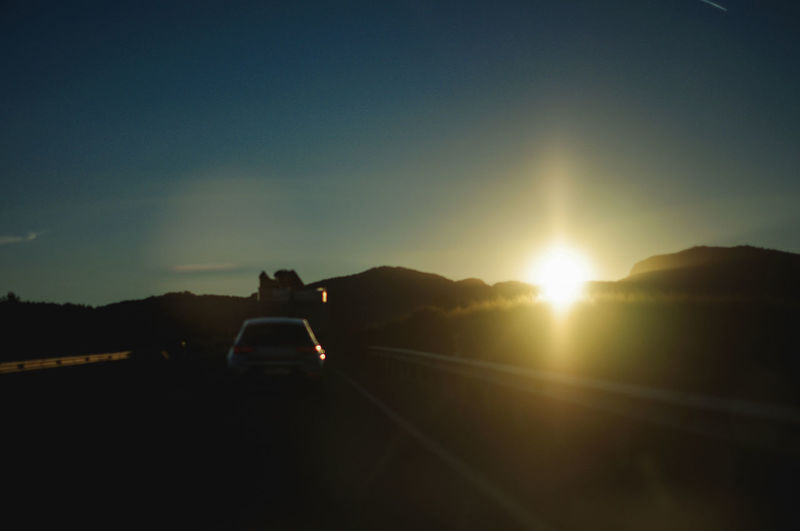 Sunset on the road Sky Transportation Sunset Mode Of Transportation Sun Nature Mountain Sunlight Car Motor Vehicle Sunbeam Environment Lens Flare Travel Road Land Vehicle Beauty In Nature Journey Silhouette Landscape Outdoors No People Road Trip on the move Copy Space