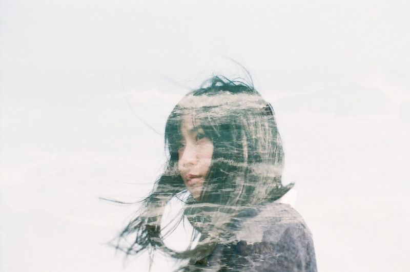 Double Exposure Of Woman And River Against Sky