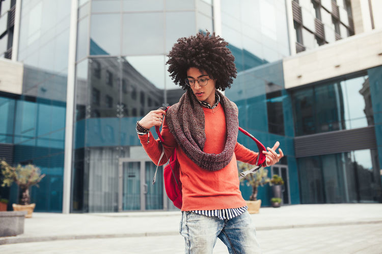 Young man wearing backpack while standing on street