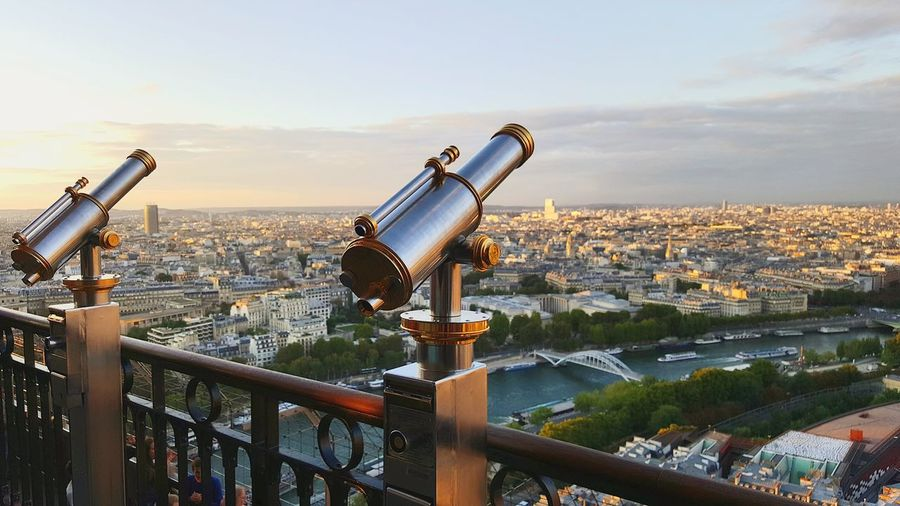 Coin-Operated Binoculars Overlooking Cityscape Against Sky