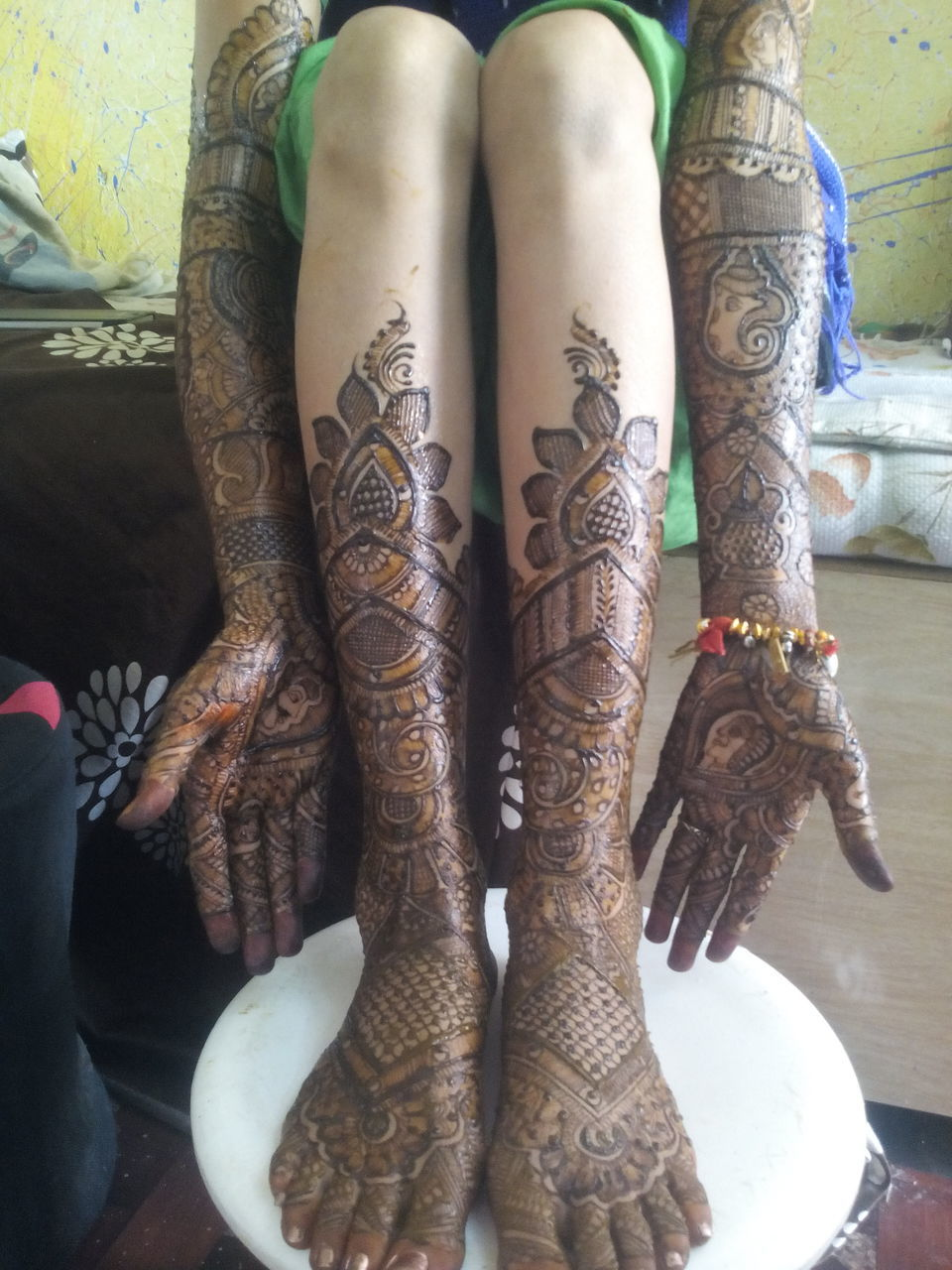henna tattoo, art and craft, creativity, real people, design, cultures, celebration, tradition, indoors, low section, close-up, human hand, women, bride, human body part, day, one person