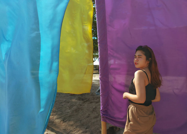 Side view of young woman standing against multi colored umbrella