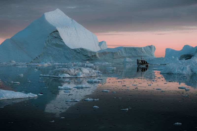 """Icebergs in a sunset depicting the color pantone of the year """"living coral"""" Water Beauty In Nature Ice Scenics - Nature Cold Temperature Sky Frozen Winter Environment Tranquil Scene Snow Reflection Tranquility Iceberg - Ice Formation Sea Glacier Idyllic Iceberg Floating On Water Boat"""