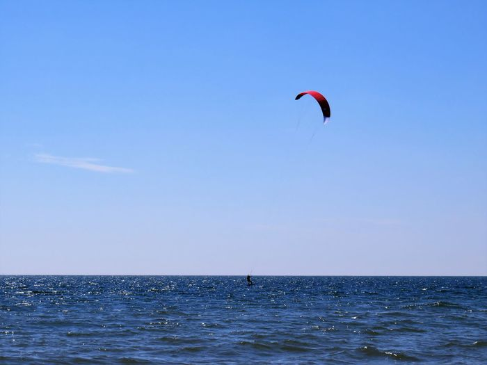 Kite flying over sea against blue sky