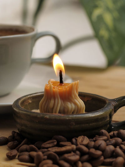 Close-up of burning candles on table