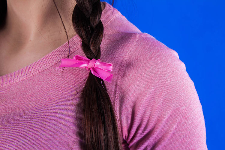 Midsection Of Woman With Braided Hair Against Blue Background