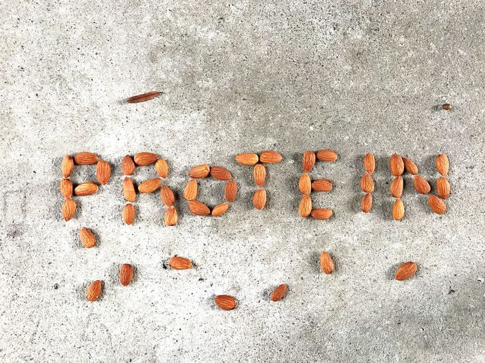 Word PROTEIN from roasted almond nuts on concrete floor Food Benefit Grey Healthy Eating Protein Food Nutrition Floor Concrete Almonds Nuts Protein Snack Protein Healthy EyeEm Selects Text Communication Western Script No People Wall - Building Feature Capital Letter Day Textured  Sign Message High Angle View Close-up Outdoors Single Word Land Information Pattern