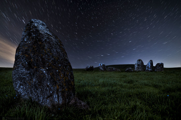 Rocks on field against sky at night