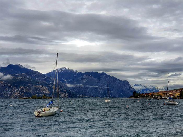 Sailboat sailing on lake against sky