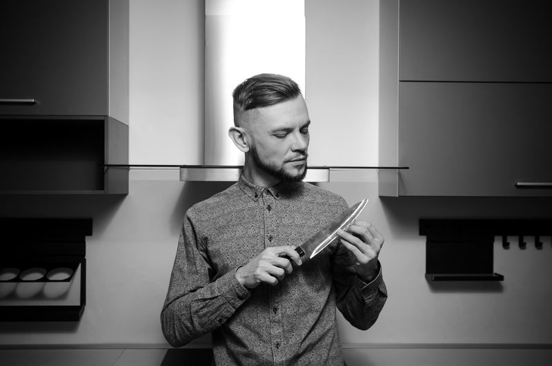 Man standing with knife at home
