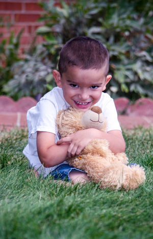 A laughing young boy sits in the grass with his favorite stuffed bear toy Bear Hanging Out Love Boy Childhood Cute Day Ethnic Favorite Toy Friendship Grass Happiness Hispanic Kid Laughter Nature One Person Outdoors Person Portrait Real People Smiling Teddy Bear