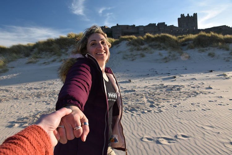 Land Beach Smiling Leisure Activity Real People Water Sand One Person Nature Happiness Lifestyles Emotion Sea Sky Portrait Women Looking At Camera Outdoors Hairstyle Blue Sky Castle Bamburgh Sandy Beach Sand Dune Tower Lookingup Looking Back Holding Hands Leading The Way Followme Follow Me Happiness Happy Relaxing Relaxation Marram Grass Joy The Portraitist - 2019 EyeEm Awards