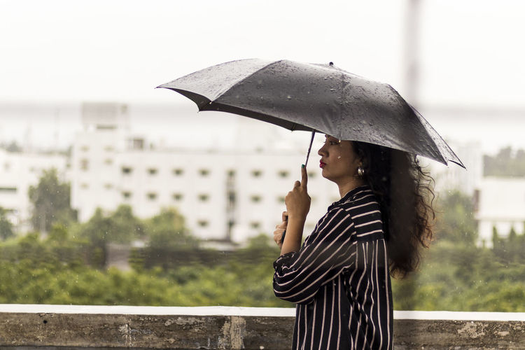 Full length of person holding umbrella standing during rainy season