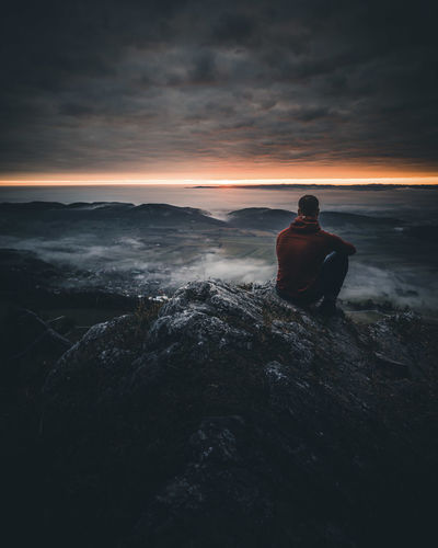 Rear view of man sitting on rock against sky during sunset