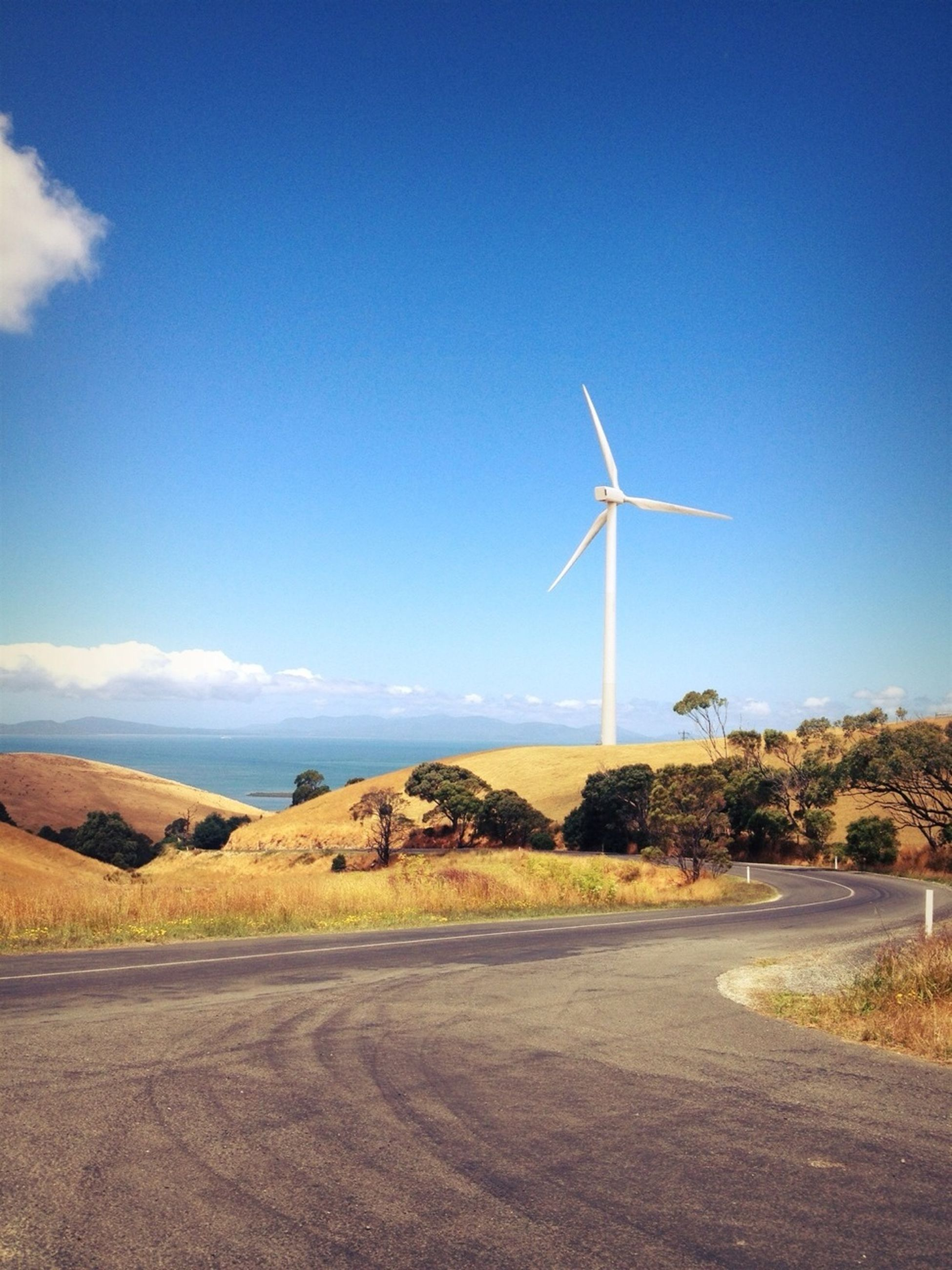 wind power, wind turbine, alternative energy, windmill, renewable energy, environmental conservation, fuel and power generation, landscape, traditional windmill, rural scene, field, technology, sky, blue, tranquil scene, tranquility, nature, road, day, non-urban scene