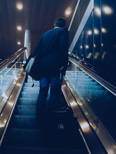 Full Length Of Businessman With Luggage In Escalator At Airport